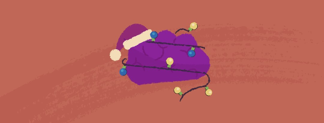 A brain with a santa hat placed upon it and a string of lights wrapped around it.