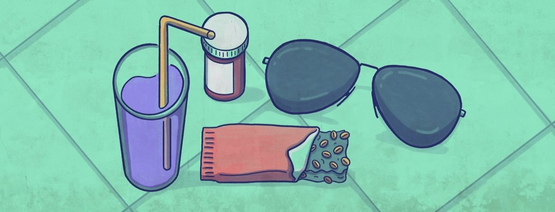 A flat lay of water, a granola bar, a medicine bottle, and sunglasses. All of these are items that the author references in their article as part of their migraine survival kit.