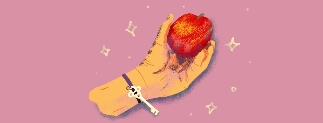 Hand with a key bracelet holding a crisp looking apple