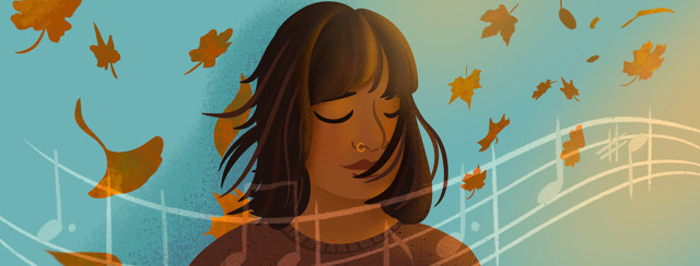 Southeast Asian woman closes her eyes while enjoying music and autumn breeze