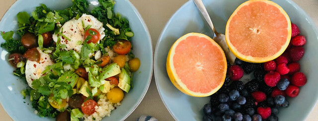 Two bowls sitting next to each other. One is full of fruit and the other full of eggs, cauliflower, tomatoes, and avocado.