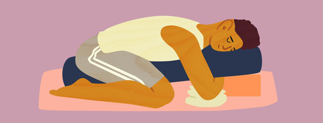 Man lays in restorative yoga pose over blocks and rolled up blankets