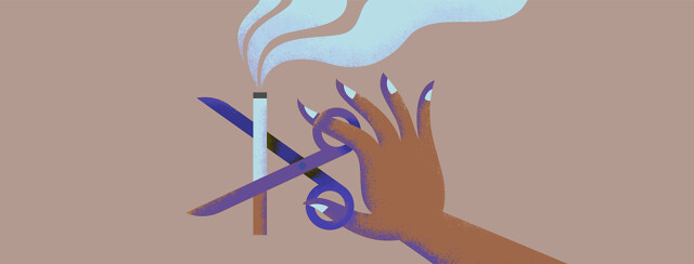 Hand with scissors snips cigarette with smoke at the tip